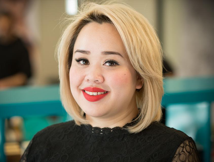 Portraitbild der asiatischen Masterstylistin im Kammpus Strese. Mai trägt einen schulterlangen blonden Bob hat rot geschmiinkte Lippen und strahlende Augen.