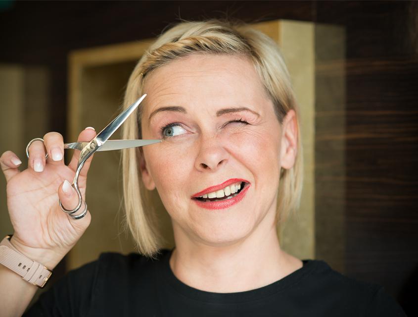 Portraitbild der blonden Salonleiterin Sabine aus dem Kammpus Strese. In einer Hand hält Sie die geöffnete Schere vor ihr zwinkerndes Gesicht.